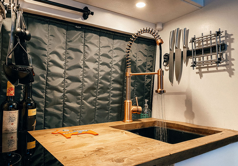 our van kitchen with copper tap and recycled scaffold worktop