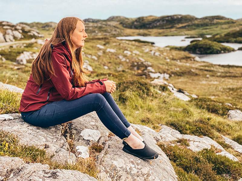Wearing mahabis curve canvas slippers sat on a rock on Harris