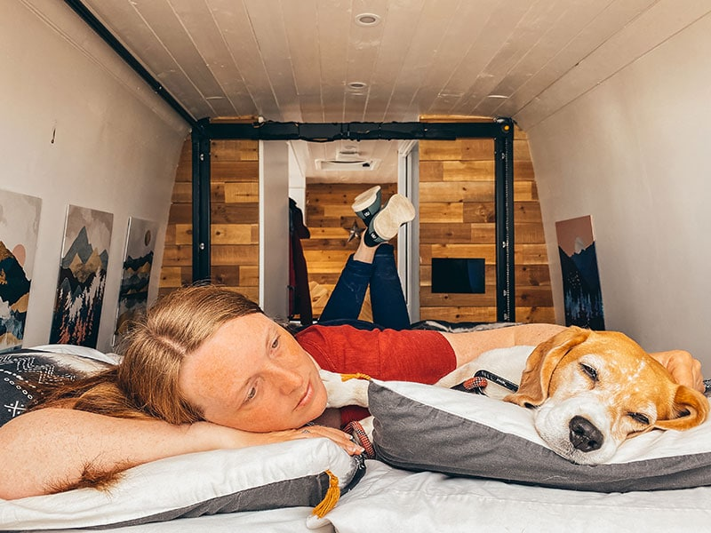 Lying on bed in camping slippers in self converted campervan with dog